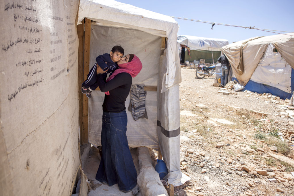 Sharifa kisses her 7-month-old daughter, Abu Adel Khalif, outside of her tent in the temporary settlement for refugees located Aarsal, Lebanon, near the border with Syria.