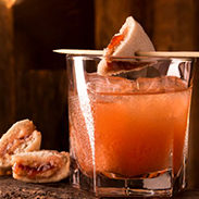 PB & J old fashioned whiskey drink with a sliced crustable sandwich as garnish